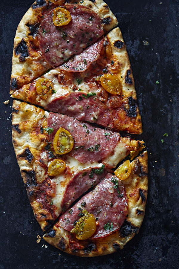 Pizza with salami, tomatoes and mozarella stock images