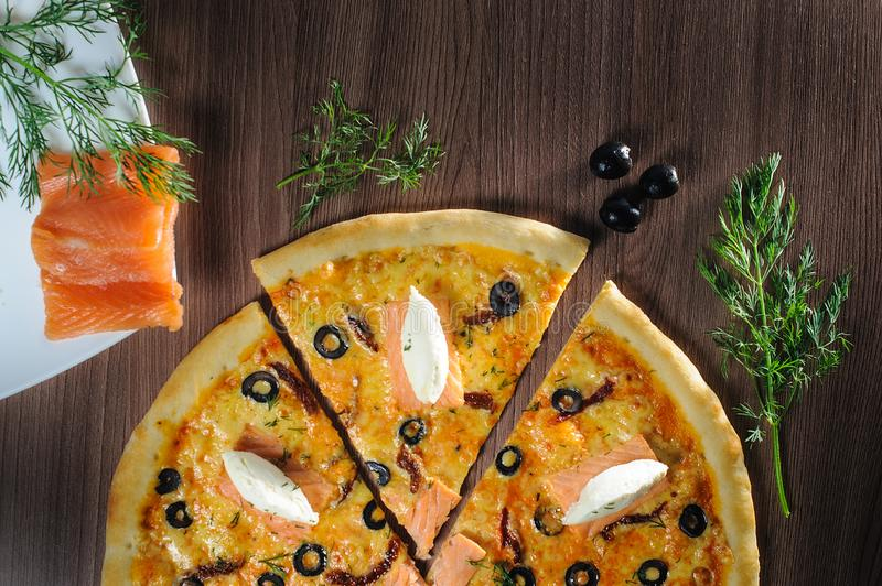 Pizza with salmon on wooden background stock image