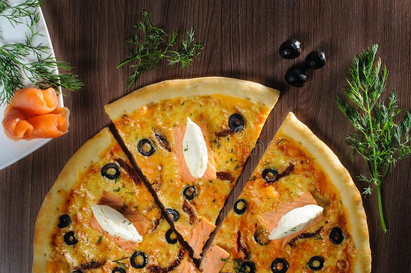 Pizza with salmon on wooden background stock photography