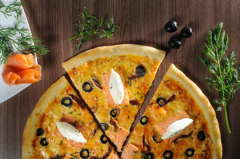 Pizza with salmon on wooden background royalty free stock image