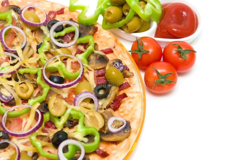 Pizza, salsa de tomate y aceitunas en un primer blanco del fondo foto de archivo libre de regalías