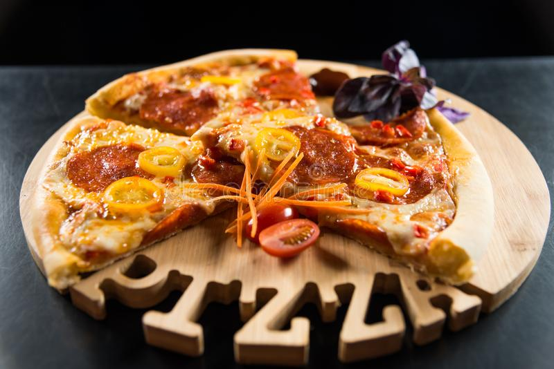 Pizza with sausage and tomatoes on a wooden round tray with a carved inscription `Pizza`. royalty free stock photography