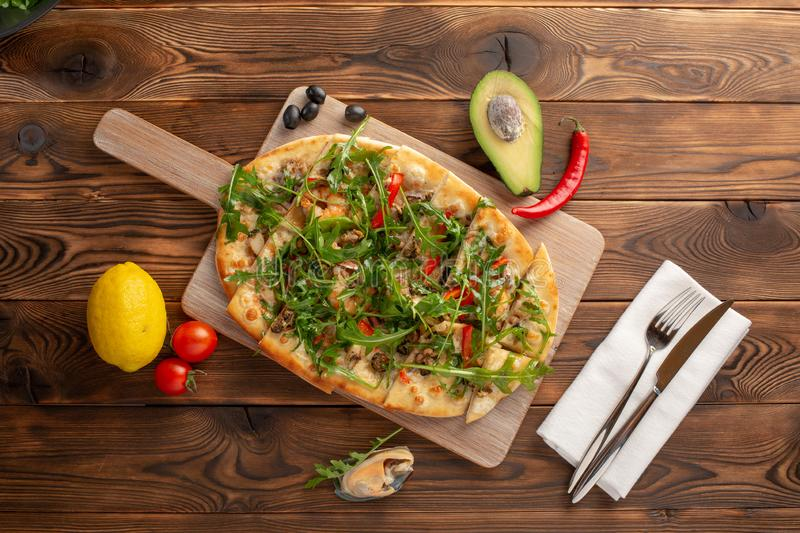 Pizza with seafood and arugula on a wooden background stock photography