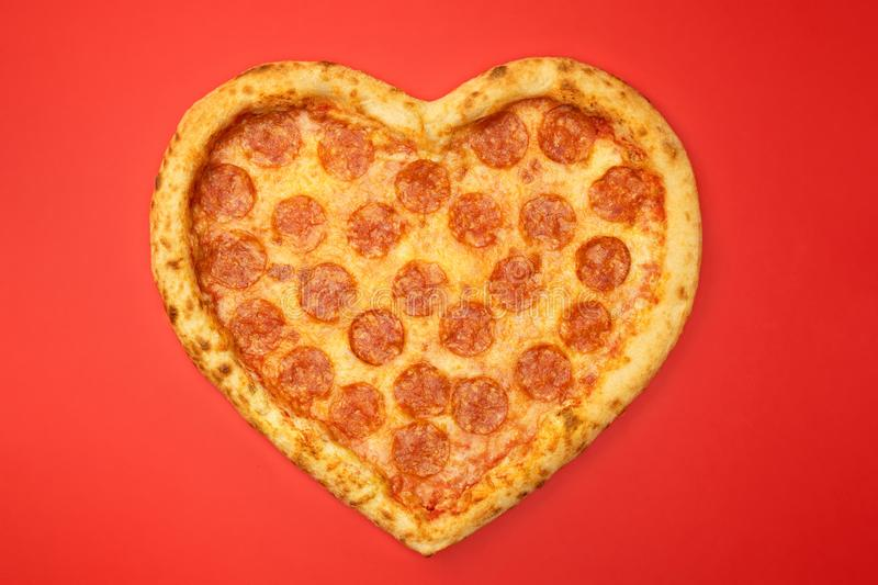 Pizza shaped heart top view Valentine`s Day on red background.  royalty free stock photos