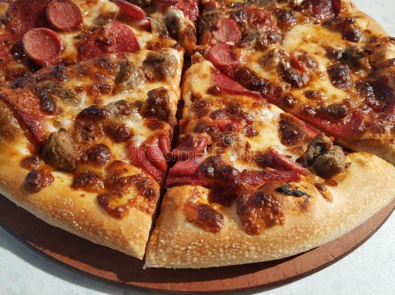 Pizza skivad pizza på tabellen royaltyfri fotografi