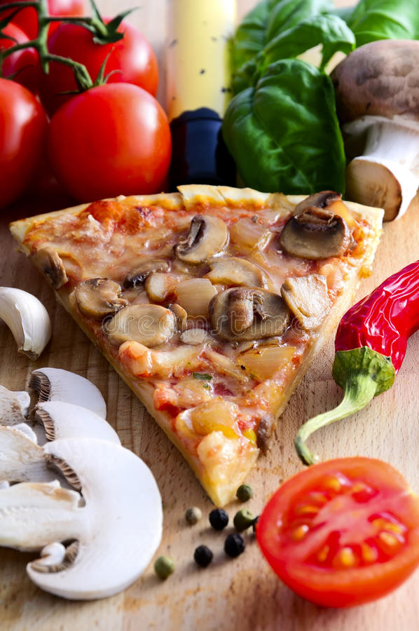 Pizza slice. And ingredients on a wooden background royalty free stock image