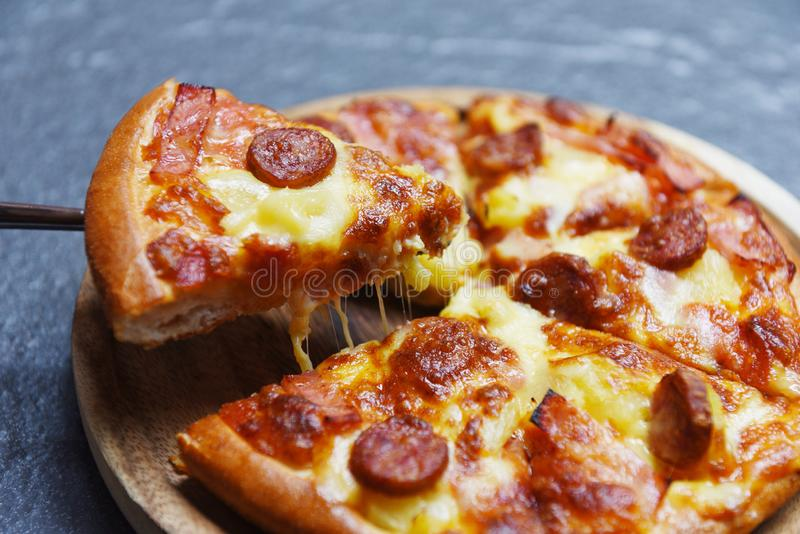 Pizza slice on dark background / delicious tasty fast food italian traditional pizza cheese stock photo