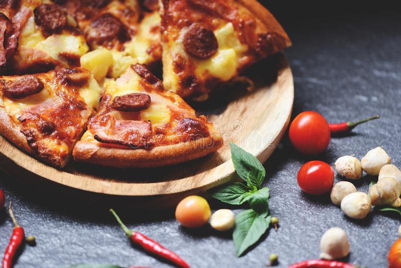 Pizza slice on wooden tray and tomato chilli basil leaf on the dark / delicious tasty fast food italian traditional pizza cheese stock images