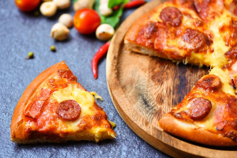 Pizza slice on wooden tray and tomato chilli basil leaf on the dark / delicious tasty fast food italian traditional pizza cheese royalty free stock photo