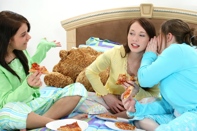 Pizza Slumber Party. Three young teen girls having pizza and whispering secrets in bed royalty free stock images