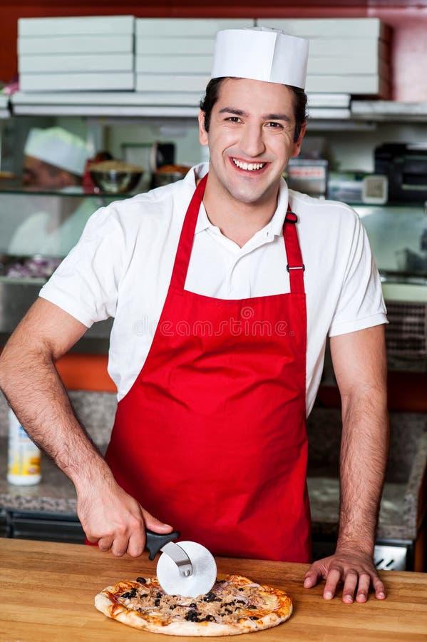 Pizza sonriente del corte del cocinero con el cortador fotografía de archivo