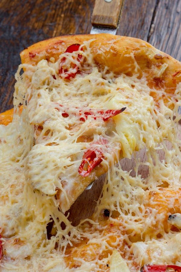 Pizza su una tavola di legno a cui aumento la classe con formaggio viscoso immagini stock libere da diritti