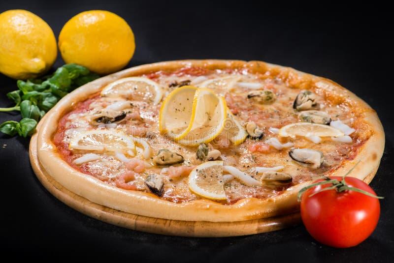 Pizza succosa deliziosa del mare con i gamberetti, il limone e l'ananas su w immagine stock libera da diritti
