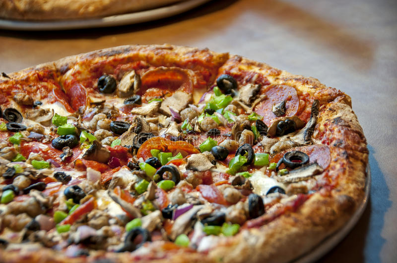 Pizza. This is a pizza supreme with lots of pepperoni and vegetables with a very nice golden crust...there is artistic blur royalty free stock image