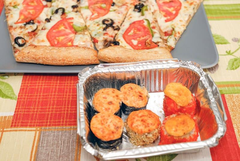 Pizza sushiThe samenstelling op de scherpe Raadspizza en de sushi voor snel voedsel Houten stokken voor sushi Vers heet voedsel stock fotografie