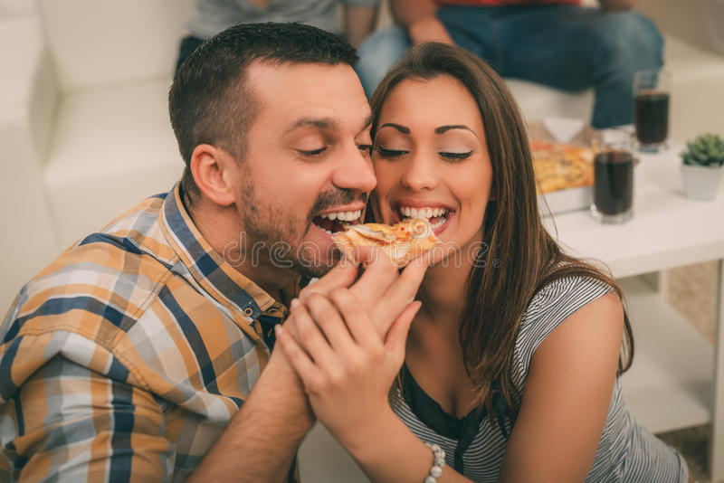 Pizza Time. Close up of a young beautiful couple sharing pizza cut royalty free stock photo