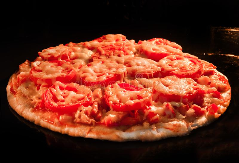 Pizza with tomatoes and cheese closeup stock images