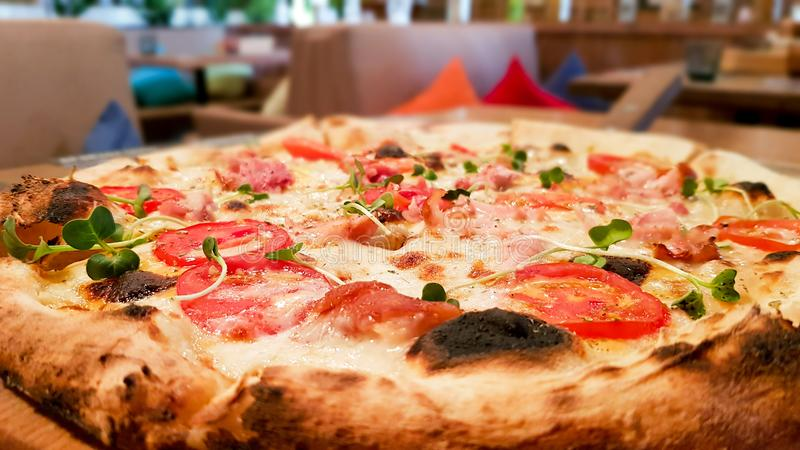Pizza with tomatoes, meat and bacon on the background of a cafe on the table royalty free stock photography