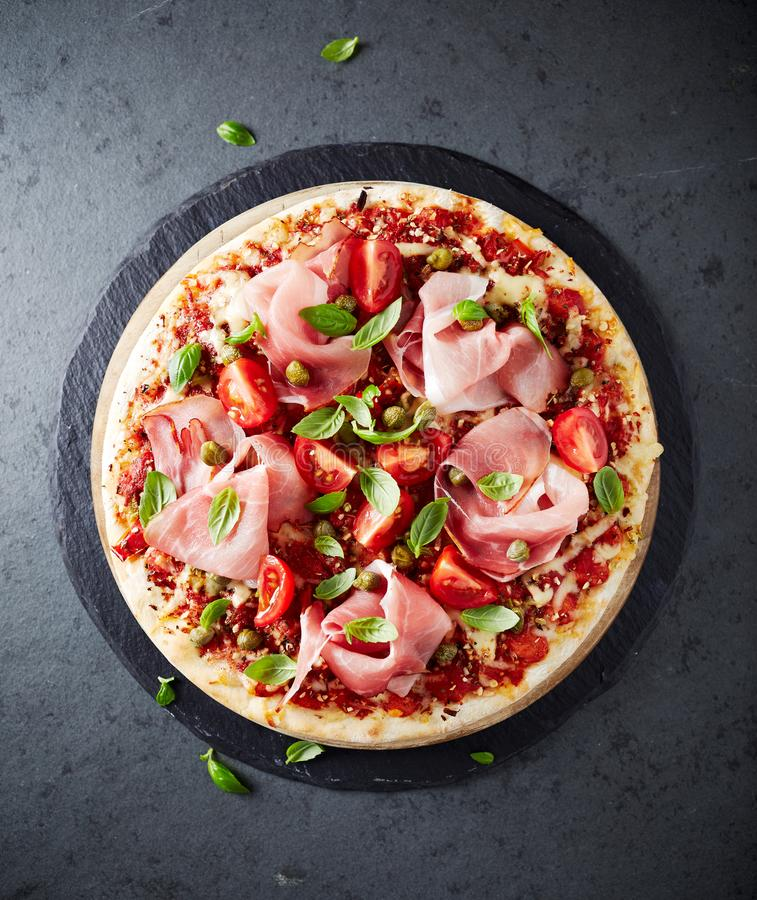 Pizza topped with black forest ham, capers and tomatoes royalty free stock photos