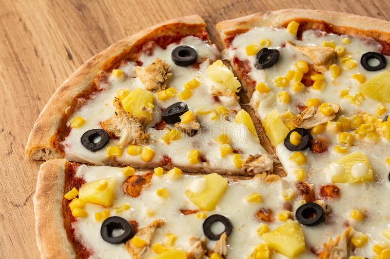 Pizza topped with sauce, chicken, cheese and pineapple serve on wooden plate on wooden table. Photo of Hawaiian pizza. royalty free stock image