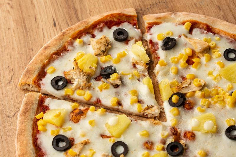 Pizza topped with sauce, chicken, cheese and pineapple serve on wooden plate on wooden table. Photo of Hawaiian pizza. stock photography