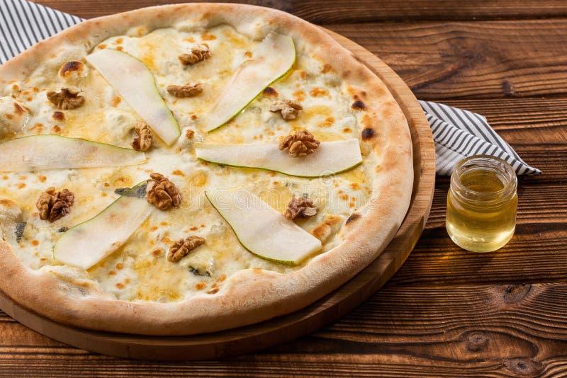 Pizza tradicional con la pera, las nueces y el queso verde en un fondo de madera Cierre para arriba Visi?n superior foto de archivo libre de regalías