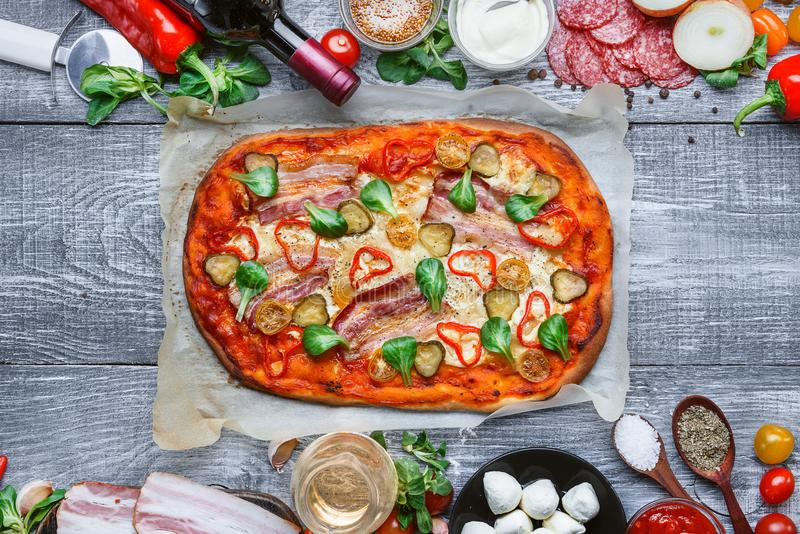 Pizza tradizionale italiana deliziosa su un fondo di legno con gli ingredienti e una bottiglia di vino rosso immagine stock libera da diritti
