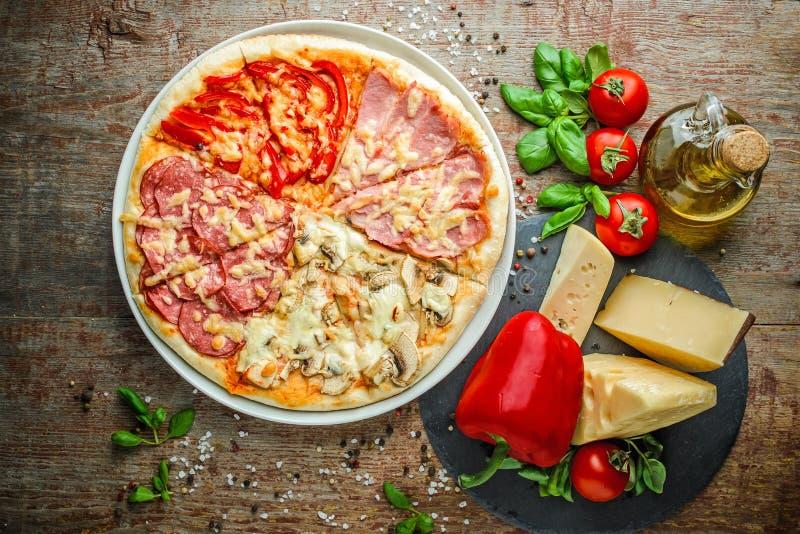 Pizza un fondo di legno di quattro stagioni immagine stock
