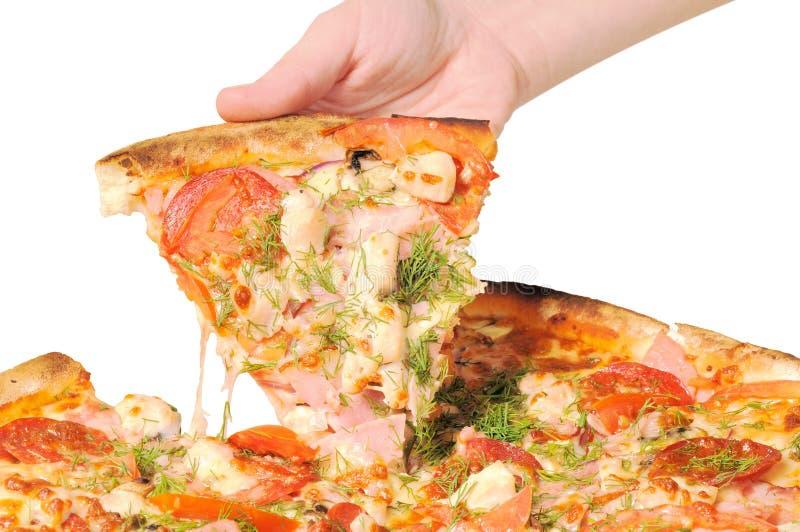 Pizza und Scheibe der Pizza in der Hand lizenzfreies stockbild