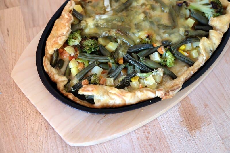 Pizza végétarienne appétissante préparée avec les légumes et le fromage dans la vue supérieure de casserole ovale noire de fer photographie stock libre de droits