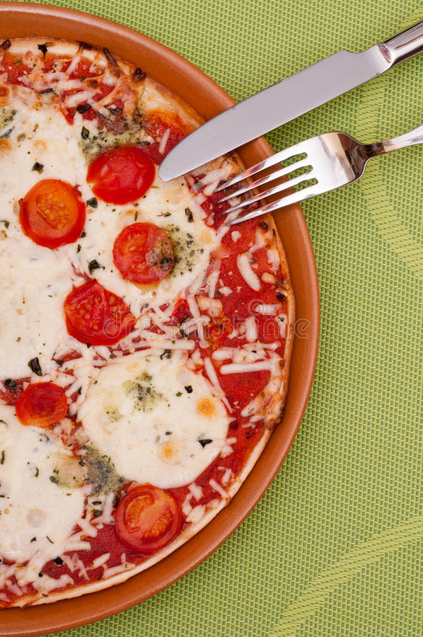 Pizza with vegetable and cheese in vertical-format. Pizza with vegetable and cheese and pesto in vertical-format stock photography