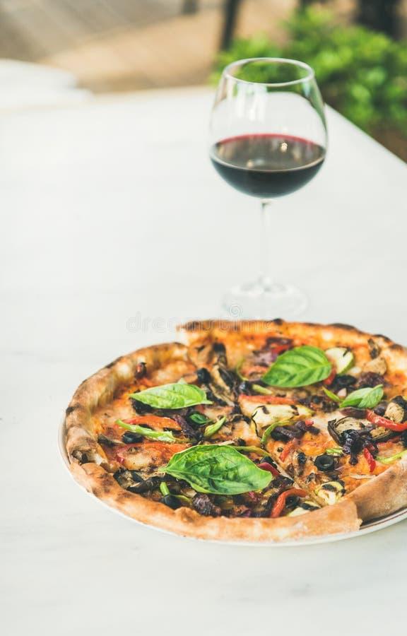 Pizza vegetariana di recente al forno e bicchiere di vino fotografia stock