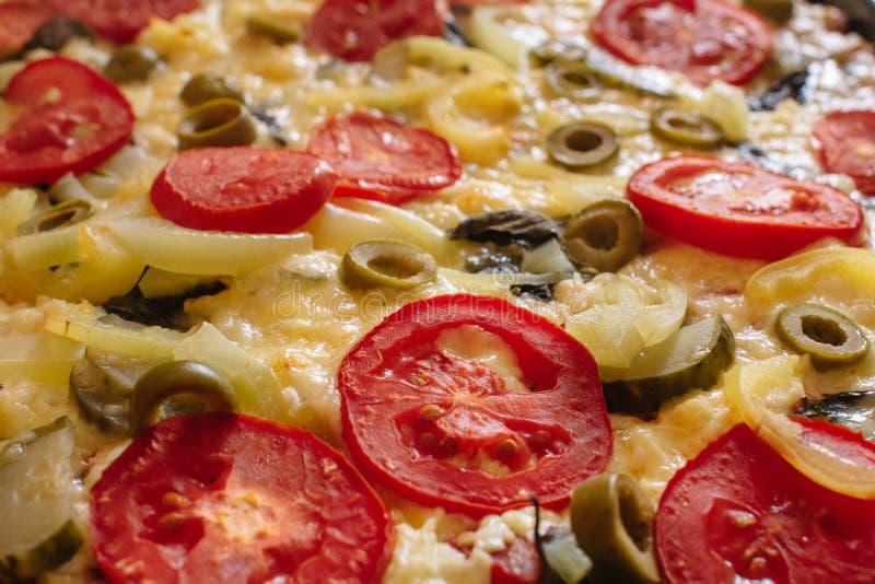 Pizza vegetariana hecha del queso, de los tomates y de las aceitunas de la mozzarella fotografía de archivo