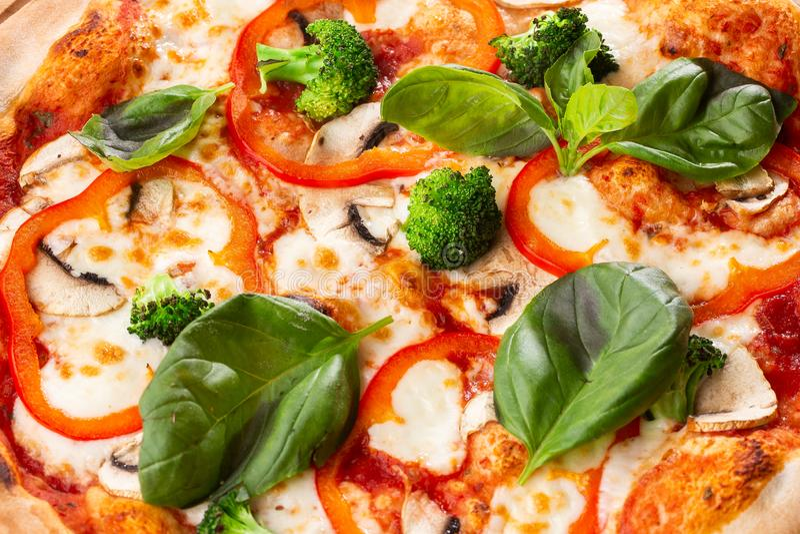 Pizza vegetariana su un fondo di legno con i funghi, broccoli, formaggio e peperone dolce e basilico Vista superiore fotografia stock libera da diritti