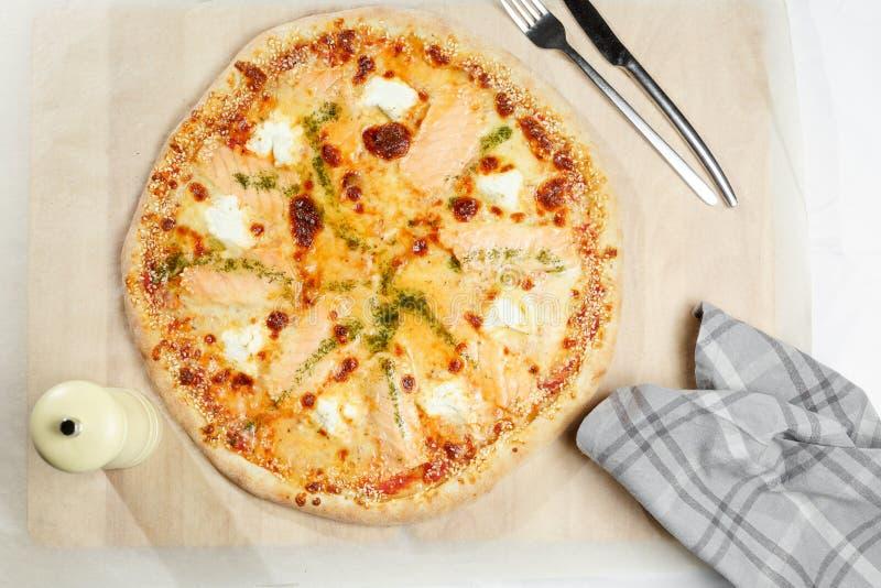 Pizza włoch z łososiem na papierze Pielucha, nóż i rozwidlenie w restauraci, zdjęcia stock