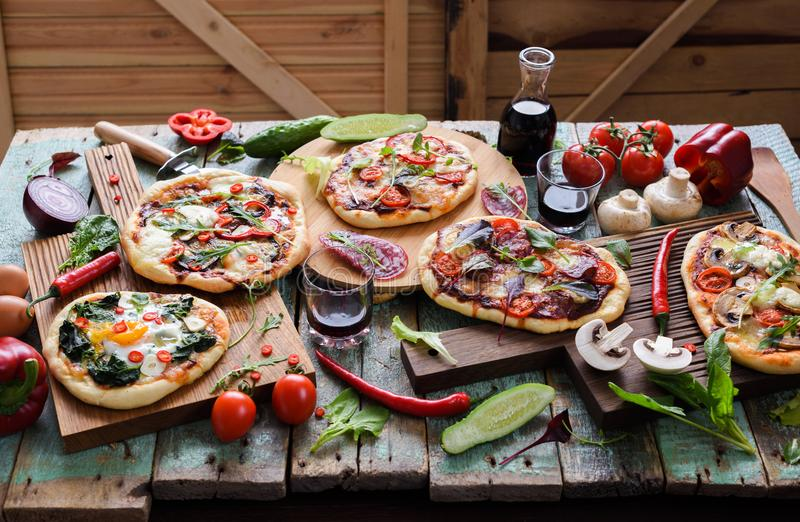 Pizza and wine party. Pizzas and raw vegetables in abundance on. Oak chopping boards over shabby blue wooden background horizontal stock photo