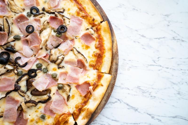 Pizza on wooden plate on table royalty free stock image