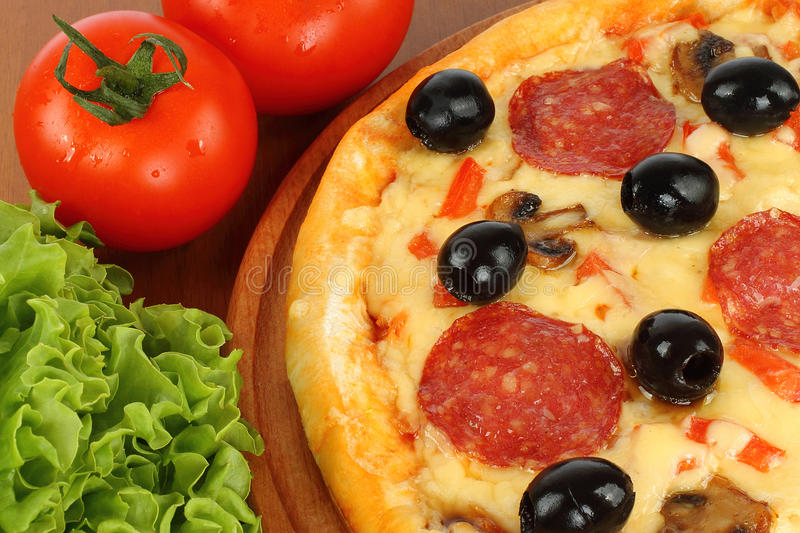 Pizza on wooden round board stock photos