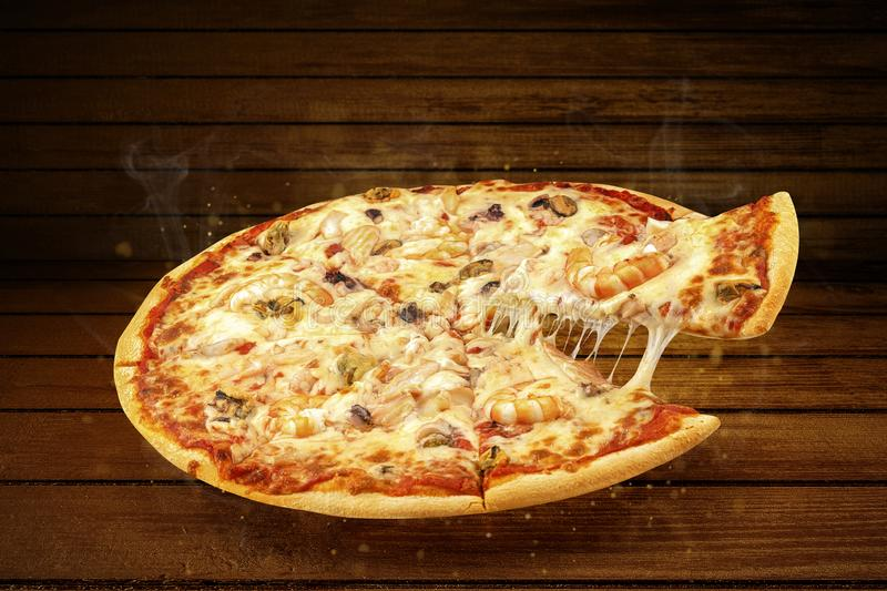 Pizza on wooden table. Flying hot pizza seafood closeup with mozzarella cheese and  steam smoke royalty free stock photos