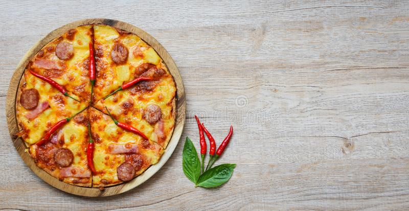 Pizza on wooden tray and chilli basil leaf top view - delicious tasty fast food italian traditional pizza cheese with Mozzarella stock photo