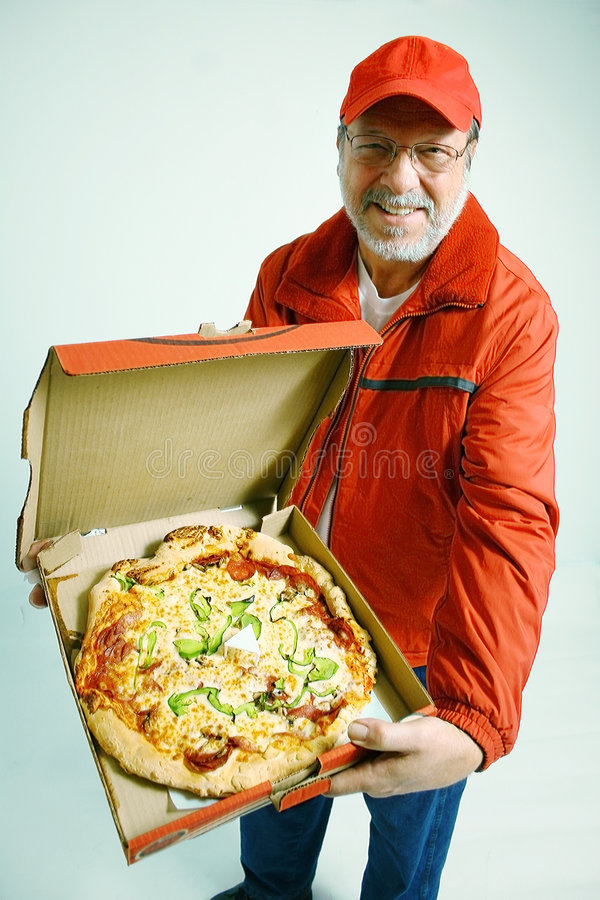 Pizza for you. Senior man with red uniform and smile delivered an all dressed pizza stock images