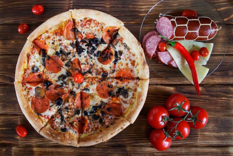 Pizza z pieczarkami, salami, pepperoni i oliwkami, kłama na wieśniaka stole przy czerwoni pieprze, pomidory, ser i kiełbasa, fotografia stock
