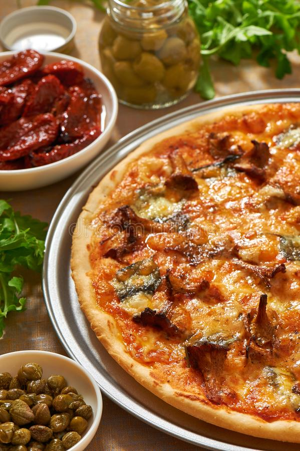 Pizza z pieczarkami, ser, basil opuszcza na aluminiowej pizzy niecce Świeży arugula, oliwki, susi pomidory i kapary, obraz royalty free