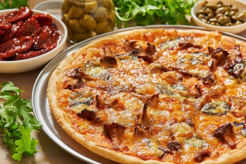 Pizza z pieczarkami, ser, basil opuszcza na aluminiowej pizzy niecce Świeży arugula, oliwki, wysuszeni pomidory i kapary, obraz royalty free
