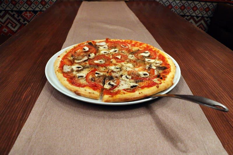 Pizza z pomidorem i pieczarkami na stole zdjęcia royalty free