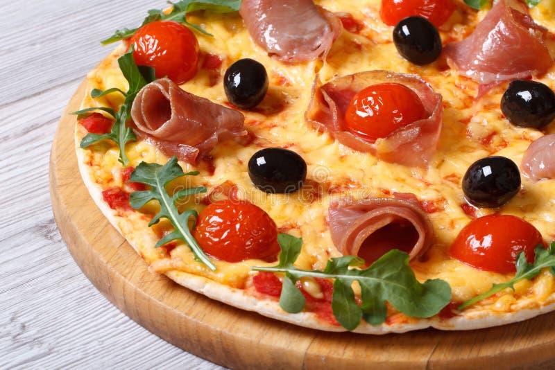 Pizza z prosciutto baleronu, pomidorów, sera i arugula zbliżeniem, obraz royalty free