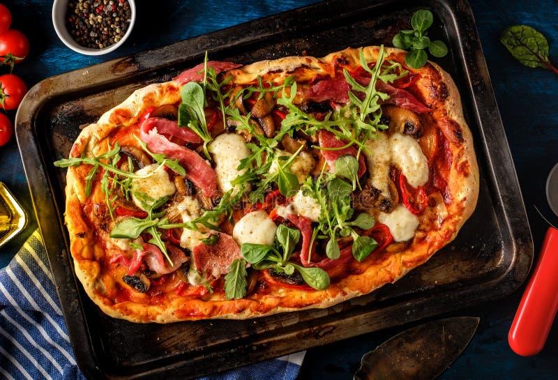 Pizza z prosciutto, mozzarelli, pieczarkowej i rakietowej sałatki dowcipem, zdjęcie royalty free