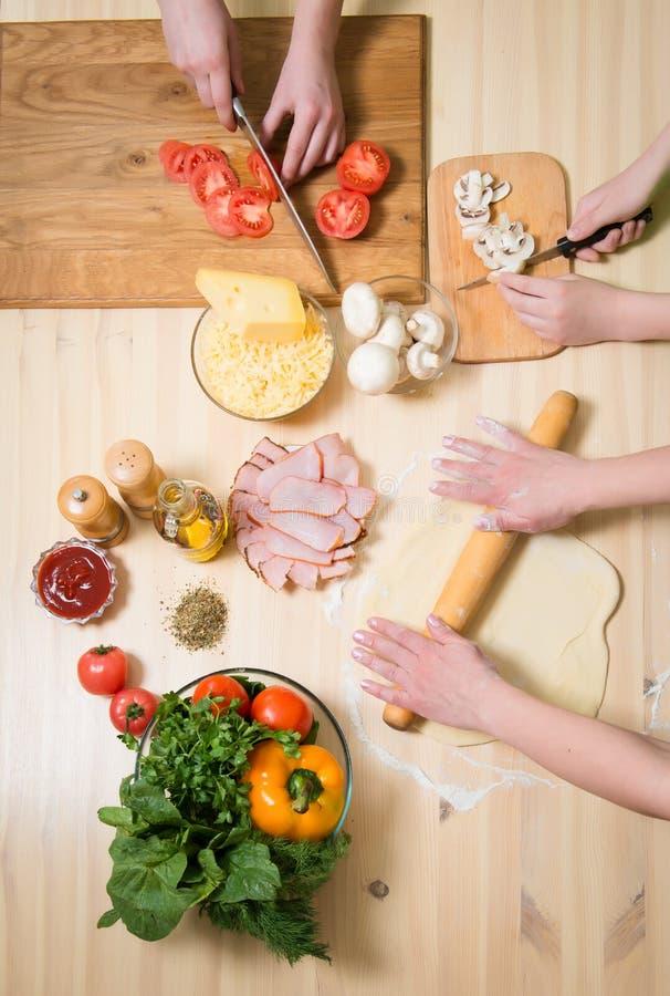 Pizza zu Hause kochen Füllende Pizza mit Bestandteilen Beschneidungspfad eingeschlossen stockfotografie