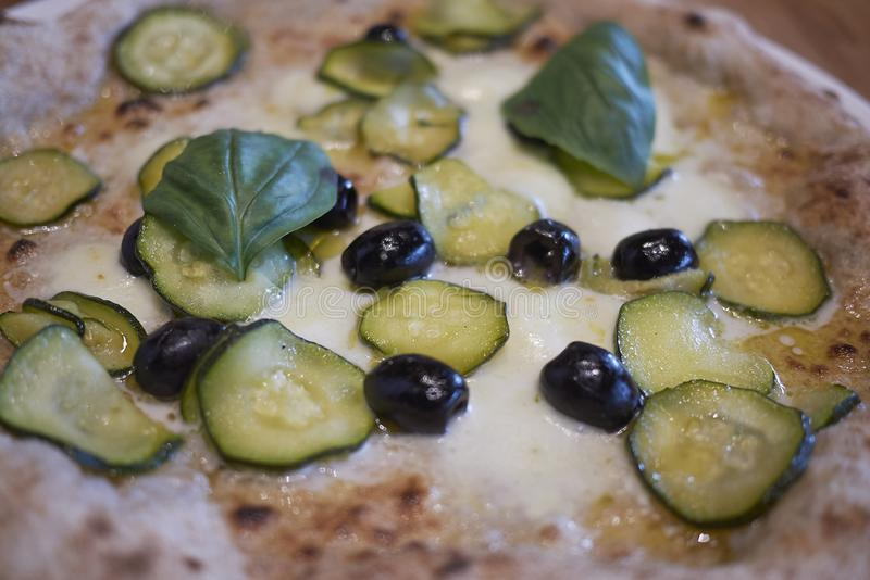 Pizza with zucchini and black olives. Closeup royalty free stock photo