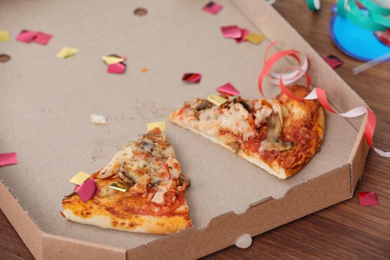Pizzaask med rester och konfettier på tabellen, closeup royaltyfri bild